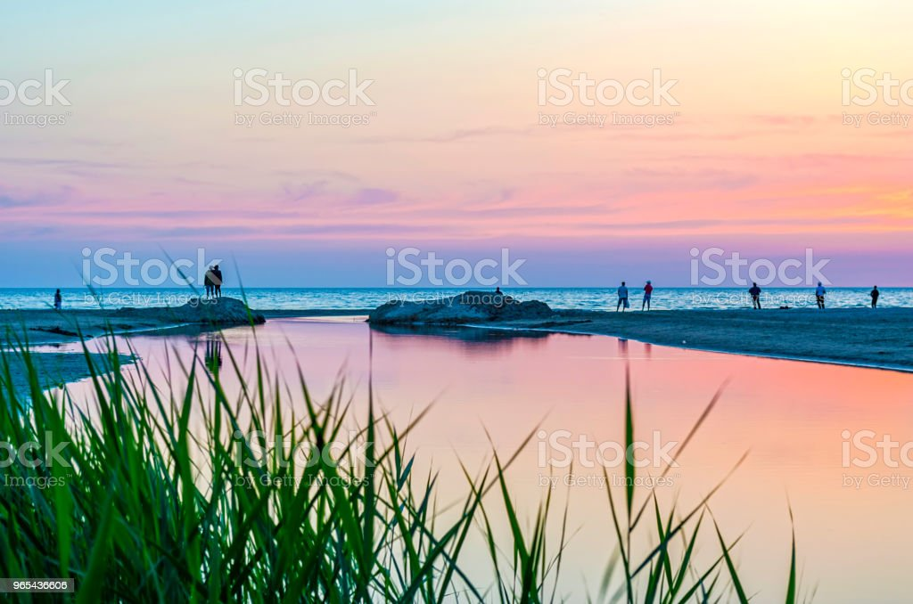 Tourists and fishermen are on the black sea and admire the beautiful sunset. royalty-free stock photo