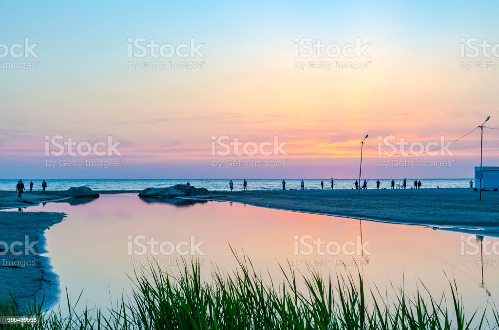 Tourists and fishermen are on the black sea and admire the sunset. zbiór zdjęć royalty-free