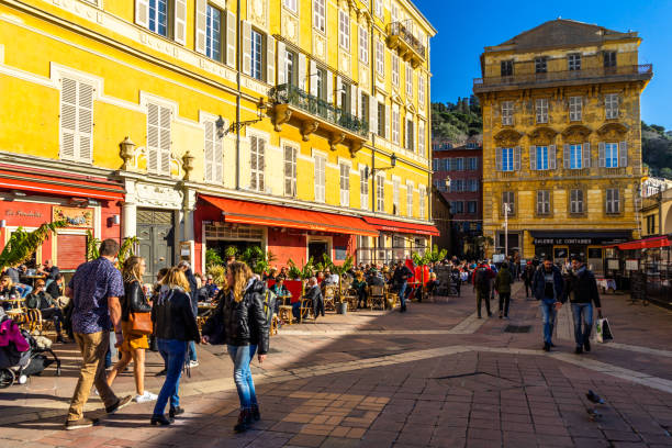 Tourists and locals enjoying a sunny day at the Cours Saleya, a lively area of Nice full of bars and restaurants, France stock photo
