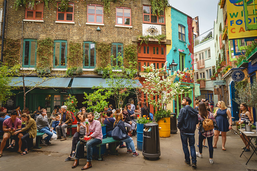 Tourists and locals in Neal's Yard, a small alley in London's Covent Garden  which opens into a courtyard. It contains several health-food cafes.