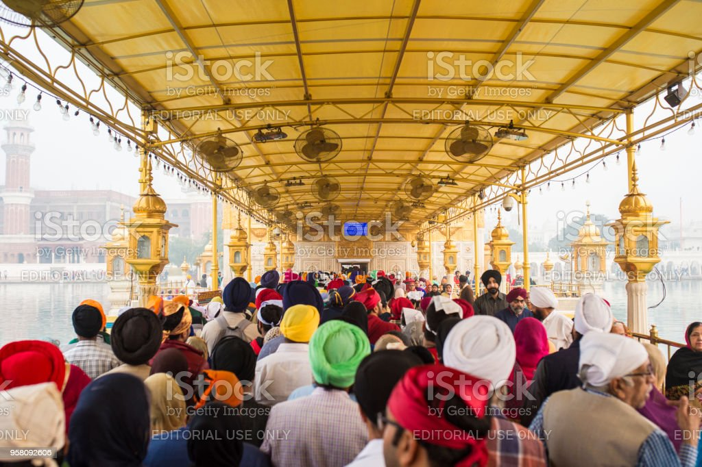 Tourists and pilgrims waiting in line at the entrance The Harmandir Sahib (Golden Temple), the holiest shrine of the Sikh religion. stock photo