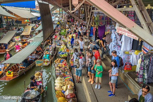 Damnoen Saduak, Thailand - April 1, 2018 : Tourists and local sellers in their boats with colorful fruits, vegetables, souvenirs and fresh food at a famous floating market near Bangkok in Thailand.