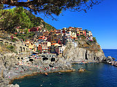 Sunbathers and tourists roam the rocky cliffs at the seaside town of Manarola which is one of the five towns of Italy's famous Cinque Terre.  It is perched above the rocky coastline of the Mediterranean Sea on a cloudless summer day.
