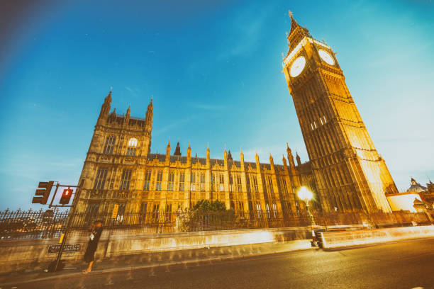 LONDON - JUNE 2015: Tourists and traffic along Westminster Palace at night. London attracts 30 million tourists annually LONDON - JUNE 2015: Tourists and traffic along Westminster Palace at night. London attracts 30 million tourists annually. annually stock pictures, royalty-free photos & images