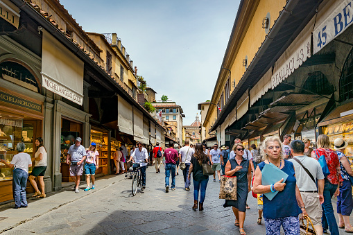 tourists and walking along the famous Ponte Vecchio in Florence, Italy