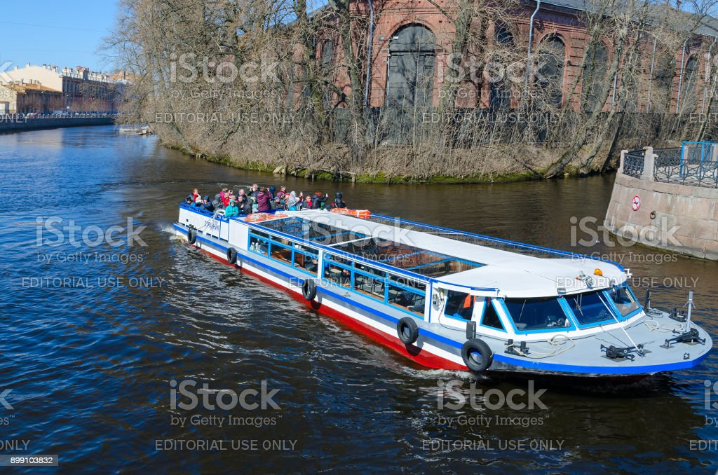 Tourists are on sightseeing boat on Moika River near forest depot, St. Petersburg, Russia stock photo