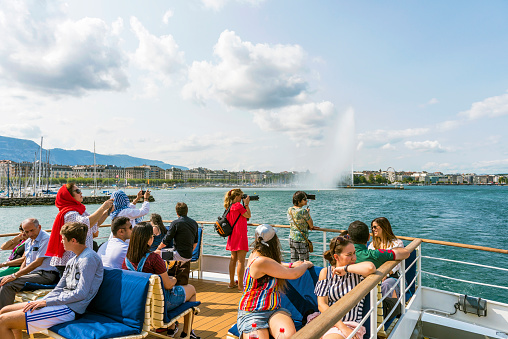 Tourists are taking photo to famous places from tourboat in Geneva, Switzerland