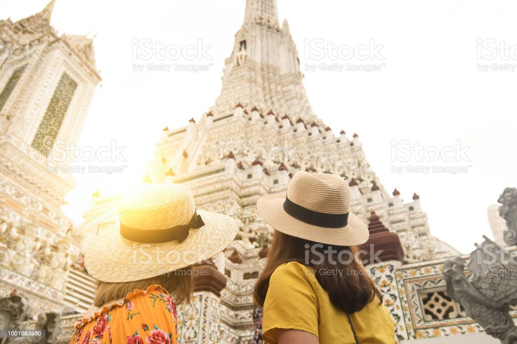 Tourists are traveling and sightseeing at Wat Arun temple in Bangkok during holiday summer vacation time. stock photo