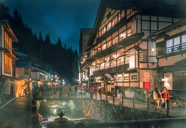 Los turistas viajan por el famoso Onsen Ginzan mientras la nieve se cae. - foto de stock