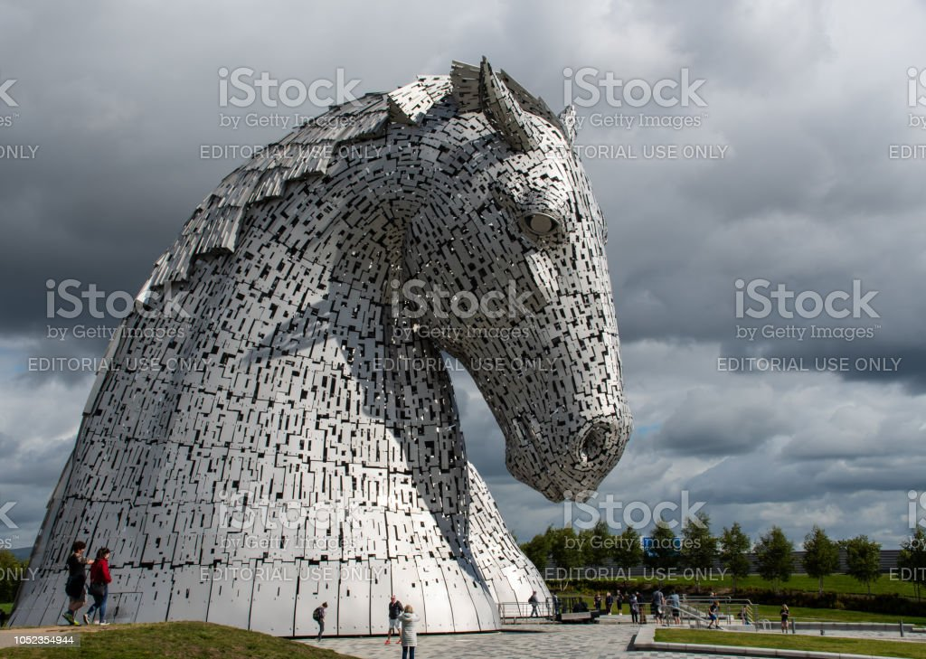 Tourists around the Kelpies - a pair of large horse head statues made from Stainless steel by Sculptor Andy Scott and unveiled in 2013 stock photo