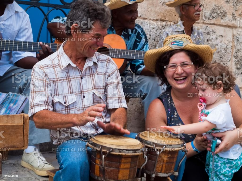 Tourists at Havana, mom and little daughter play with street musicians, Cuba stock photo