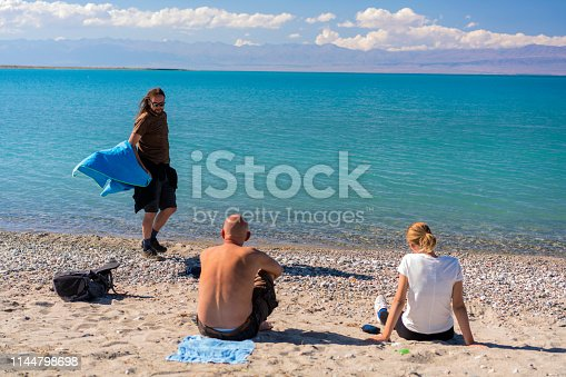 Tourists, senior and young ones, having fun while sun bathing and drying towels, clothes after swimming in Issyk-Kul Lake. Kyrgyzstan.