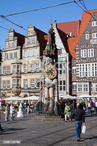 Tourists at medieval Roland statue of Bremen. Statue is from 1404 and is part of unesco heritage with square. In background are old row houses and tables of restaurants under parasols