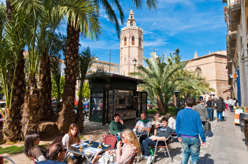 Tourists at pavement cafe palm trees El Micalet Valencia Spain