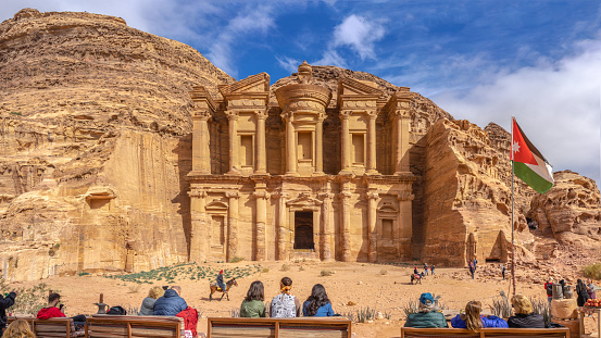 PETRA, JORDAN - January 13  2020: Nabatean ancient city of Petra. Facade of the Ad Deir The Monastery with tourists Temple In Petra In Jordan