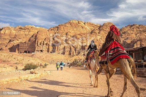 Petra, Jordan - January 13, 2020: tourists walking along the Sik canyon to the treasure of Petra (Al Khaznen), Jordan. UNESCO Heritage