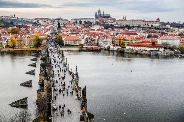Tourists at Prague Charles Bridge. Prague with Vltava river. Cityscape with mass tourism stock photo