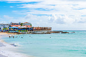 Philipsburg, Sint Maarten - November 16 2018: Sunset Beach and Bar SXM on sunny day with tourists taking a swim and at Restaurant on coastal shore. Tropical Caribbean island vacation setting.
