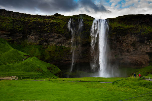 Tourists at the basis of Seljandsfoss waterfall in Iceland during a cloudy and windy summer day South-East Iceland tuff stock pictures, royalty-free photos & images