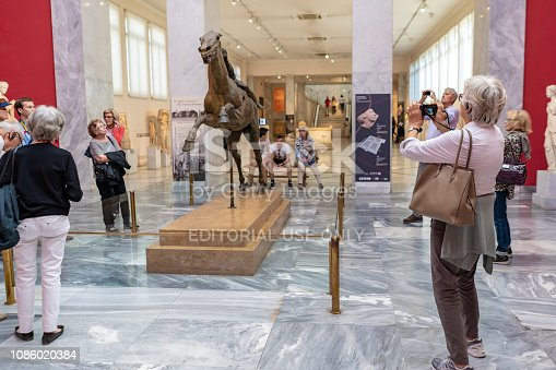 Athens, Greece - October 19, 2018: A tourist takes a photo of the famous  Jockey of Artemision sculpture created in 150 B.C.