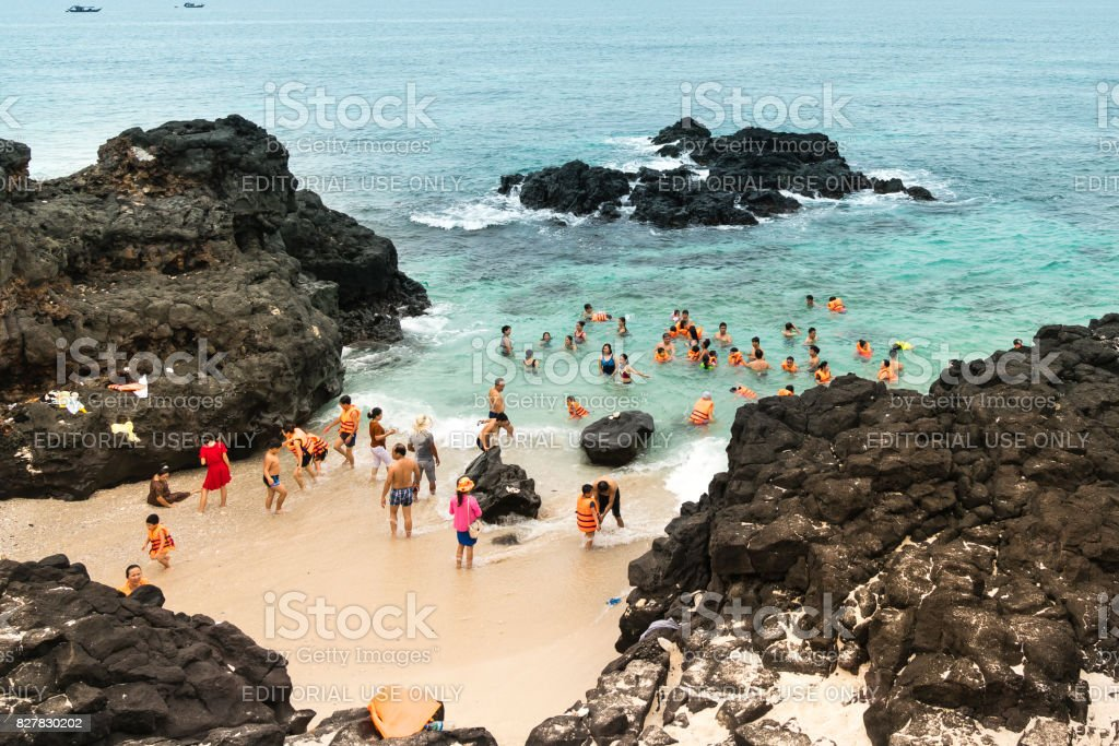 Tourists bathing and experiencing the waves and clear  water stock photo