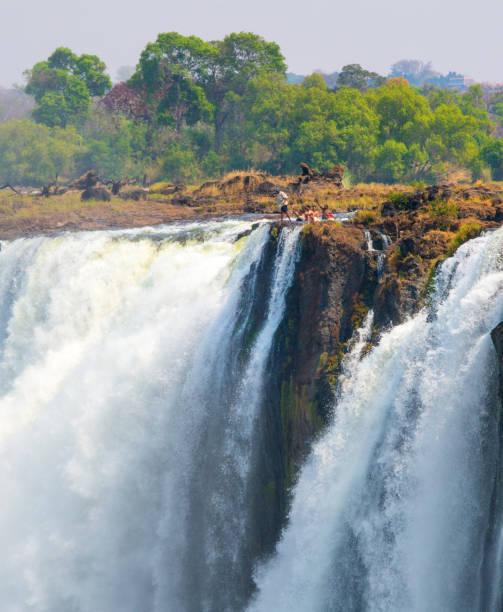 tourists bathing in devils pool - victoria falls - fluss sambesi stock-fotos und bilder