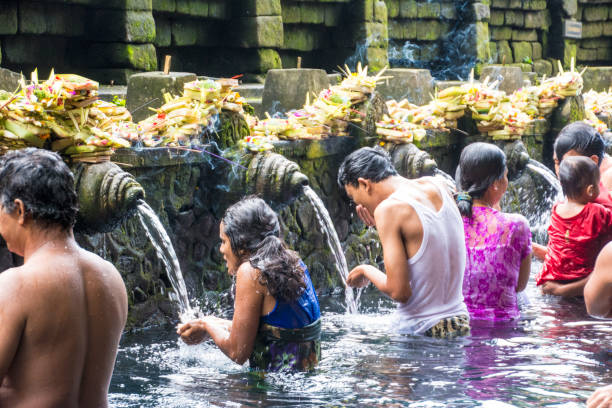 tourists bathing in the holy water at pura tirta empul temple, tampaksiring, bali, indonesia - religious celebration stock photos and pictures