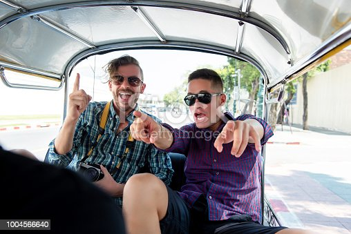Two tourist man friends being excited and having fun on local Tuk Tuk taxi while traveling in Bangkok city, Thailand