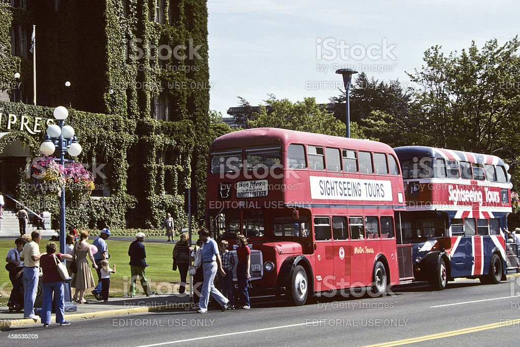 Tourists Board a Double Decker Bus at the Empress Hotel stock photo