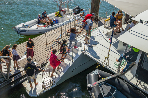 Tourists boarding an UBA boat, the shuttle between Arcachon and Cap Ferret, docked at a jetty on a summer day