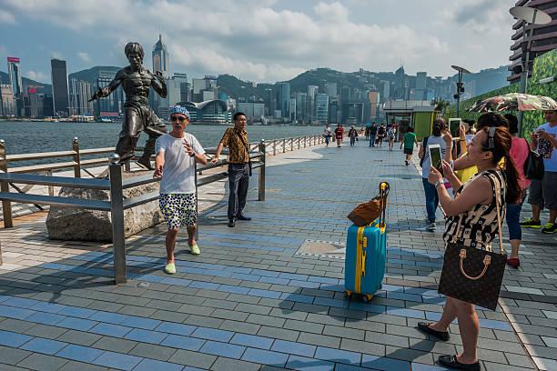 Os turistas Bruce Lee estátua Avenida das estrelas de Hong Kong - foto de acervo