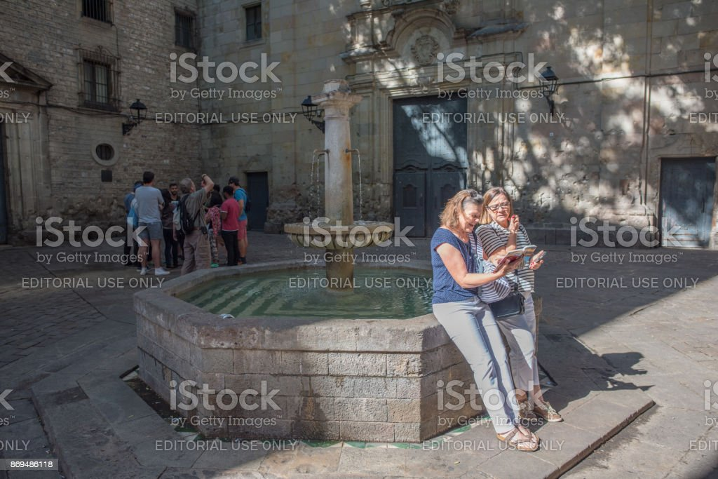 Tourists check their guidebook in Felip Neri Plaza in Barcelona stock photo
