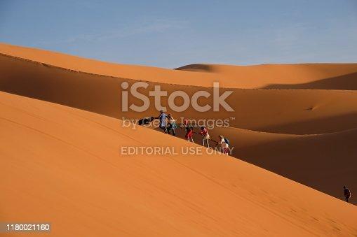 Merzouga /Morocco -april 2018: Several tourists climbing on dunes of Sahara desert under daylight. Near the village of Merzouga in Morocco