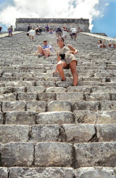 touristen erobern chichen itza hauptpyramide. konfessionslos besucher kukulkan pyramide in chichen itza, yukatan. kukulkan pyramide ist eine der sieben neuen weltwunder und beliebtes touristenziel in mexiko. - typisch 90er stock-fotos und bilder
