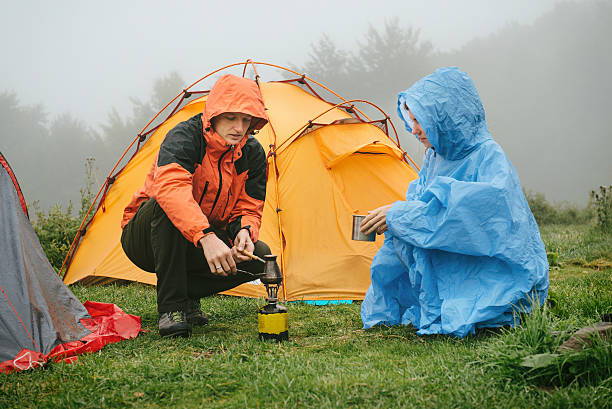 Tourists cooking coffee near tent in the mountains - Photo