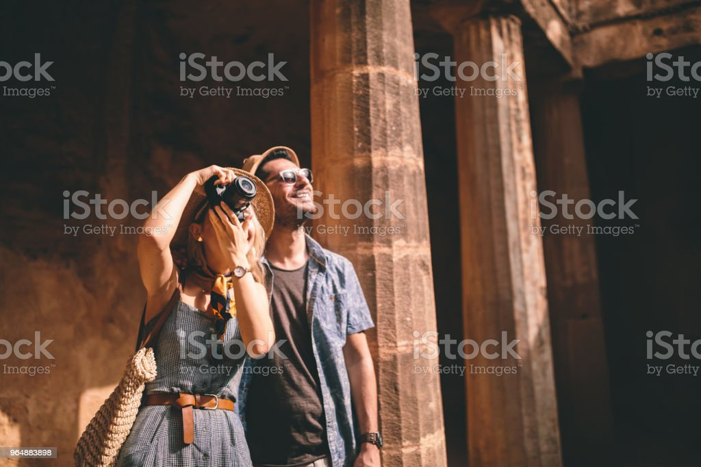 Tourists couple doing sightseeing and taking photos of archaeological site royalty-free stock photo