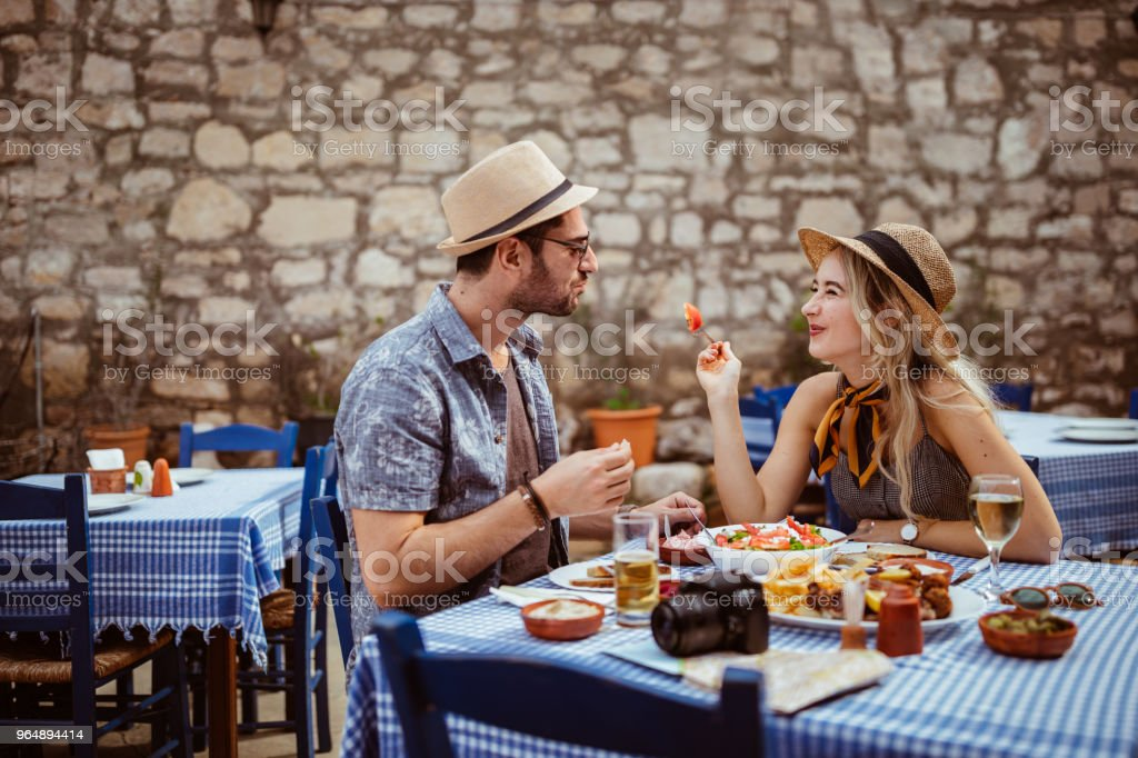 Tourists couple having fun eating lunch at traditional Spanish restaurant royalty-free stock photo