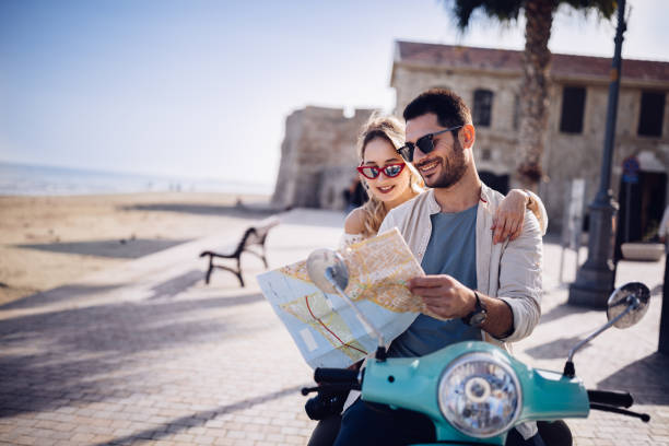 Tourists couple with retro scooter reading map on Mediterranean island stock photo