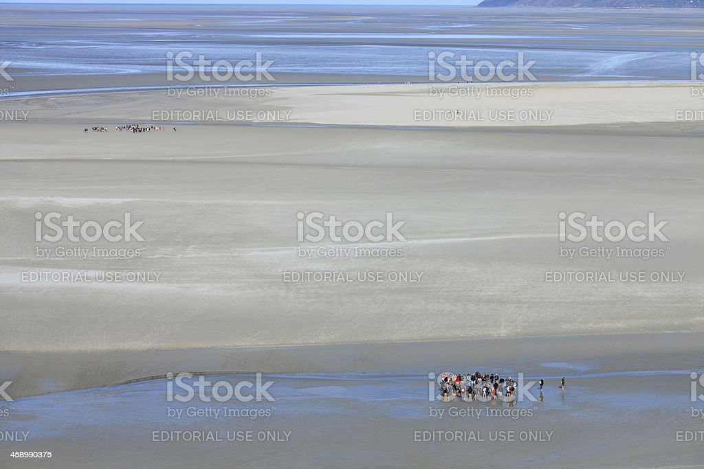 Tourists crossing the water at low tide royalty-free stock photo