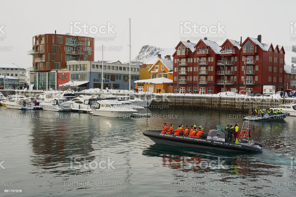 Tourists depart for boat safari from the harbor of Svolvaer, Norway. stock photo