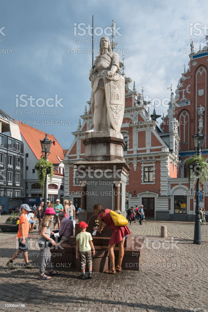 Tourists  drinking water in the Old Town Square, next to statue of Roland  and Blackheads house stock photo