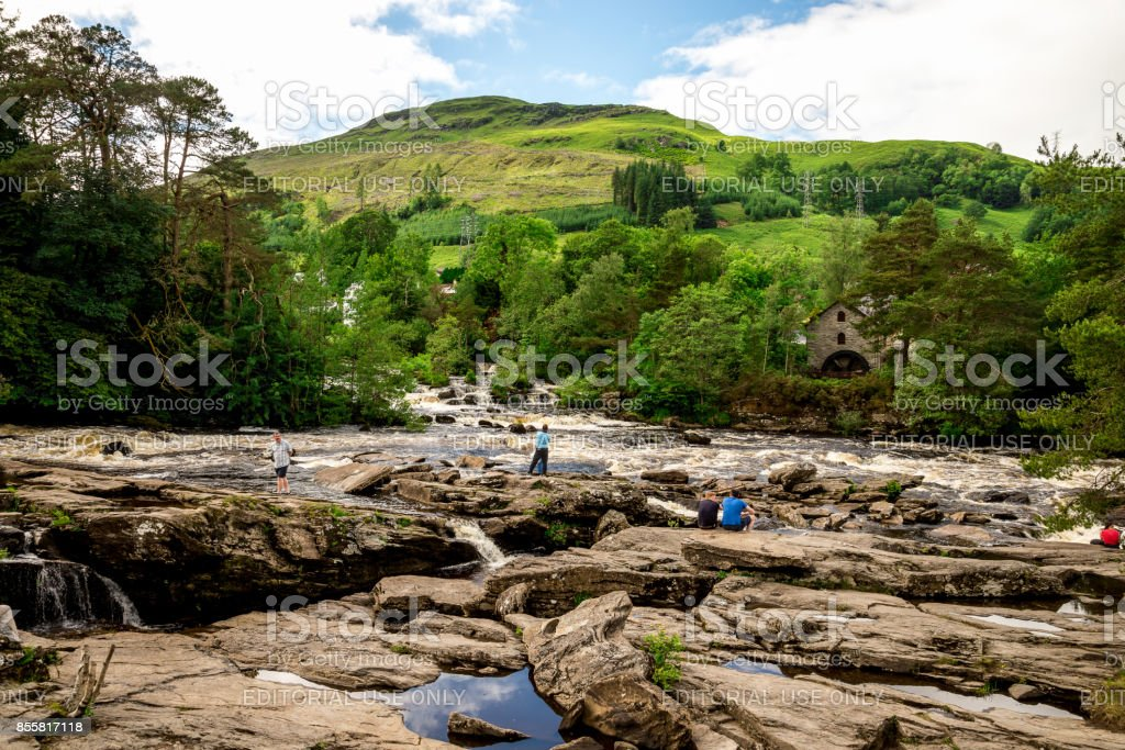 Tourists enjoy falls of Dochart view and hill landscape in a town of Killin, central Scotland stock photo