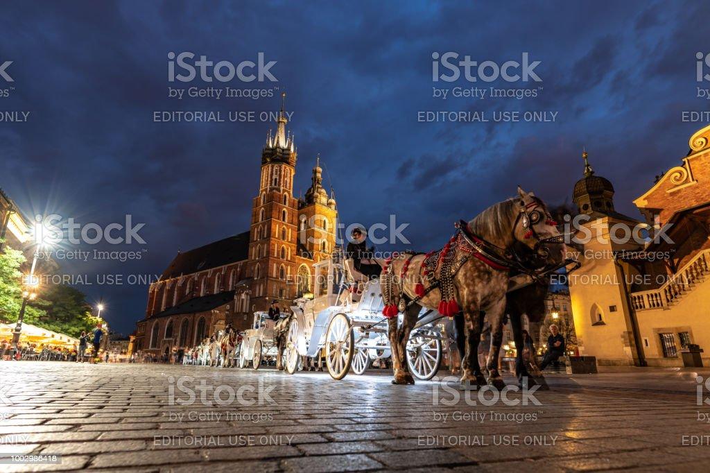 Tourists enjoy horse drawn carriage rides around old town Krakow, Poland at night stock photo