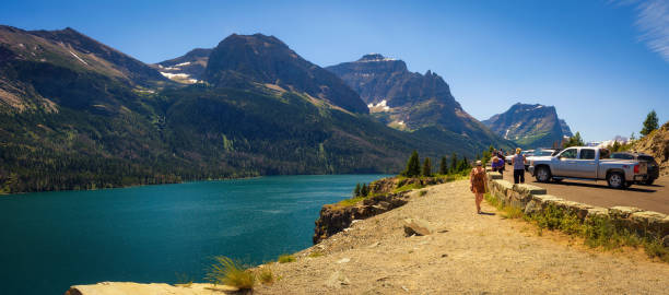 tourists enjoy the view of saint mary lake in glacier national park - st. mary lake stock pictures, royalty-free photos & images