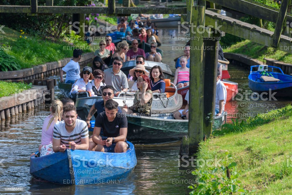 Tourists enjoying a boat tour on the canals of Giethoorn in The Netherlands stock photo