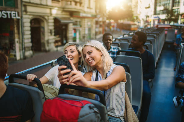 Tourists Enjoying Open Top Bus Tour In The City stock photo