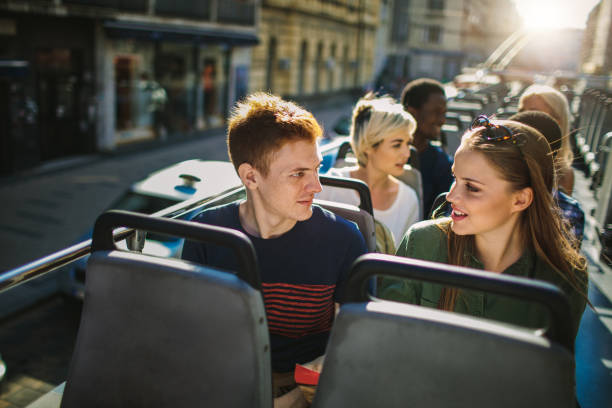 touristen genießen open top bustour in der stadt - tour bus stock-fotos und bilder