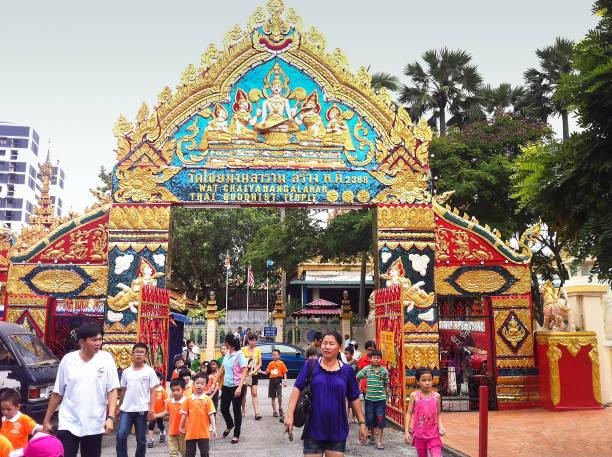 tourists entering into Wat Chaiyamangalaram Thai buddhist temple in Penang stock photo