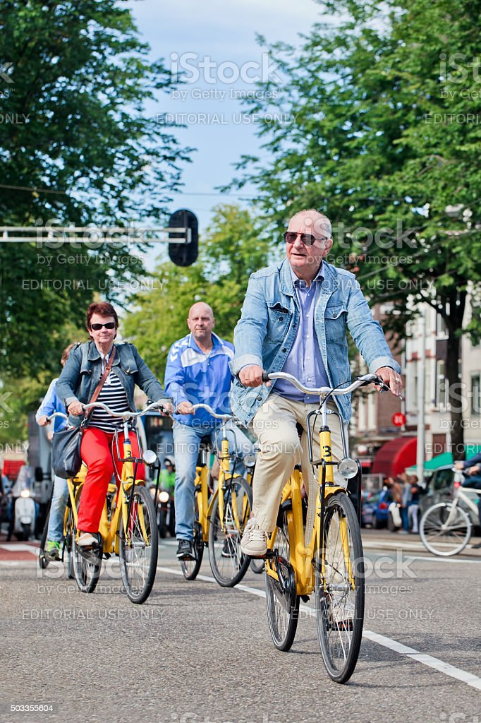 Tourists explore Amsterdam city center on rental bikes stock photo