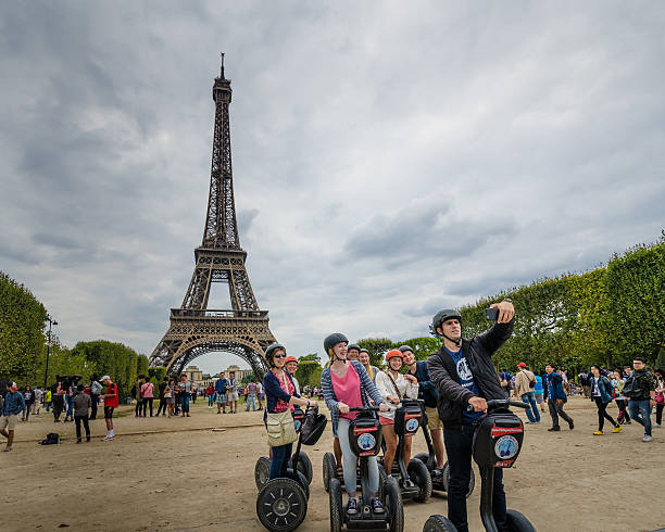 Tourists explore the grounds of the Eiffel Tower on Segways stock photo